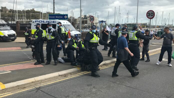 Police restrain anti-immigration protesters on the ground by the entrance to Dover harbour