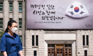 As a precautionary measure, a woman wearing a face mask walks under the banner of the campaign on the wall of Seoul City Hall in South Korea.