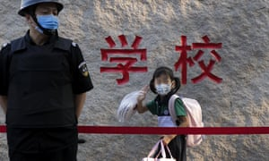 A student wearing a face mask to prevent the spread of coronavirus waves next to a masked security guard as he enters an elementary school in Beijing on Monday, September 7, 2020.