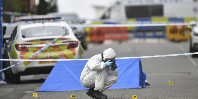 A police forensics officer taking photographs in Birmingham after stabbing several people in the city center on Sunday.  (AP / PA)