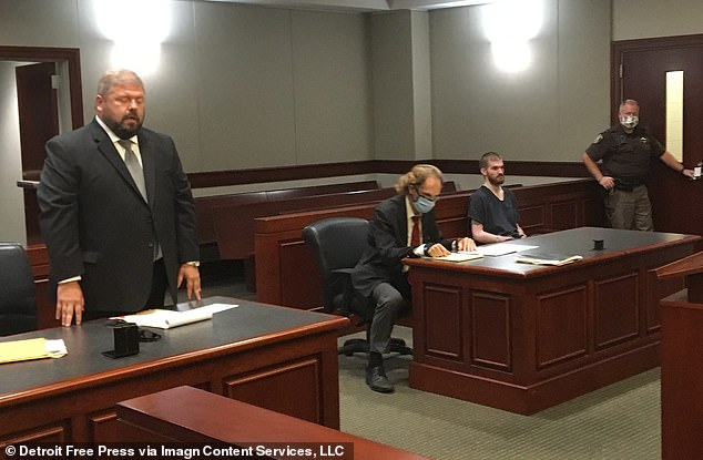 Hughes, sitting to the right, appeared in court Wednesday.  He faces charges of first-degree domestic assault and malicious destruction of property.