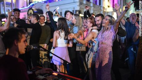 People are spotted dancing on a baker in Leicester Square in central London on September 12, just days before the ban on social gatherings again.
