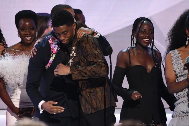 """Michael B. Jordan (L) congratulates Chadwick Boseman (C)  as the cast of """"Black Panther"""" accepts an award at  the 25th Annual Screen Actors Guild Awards on Jan 27, 2019."""