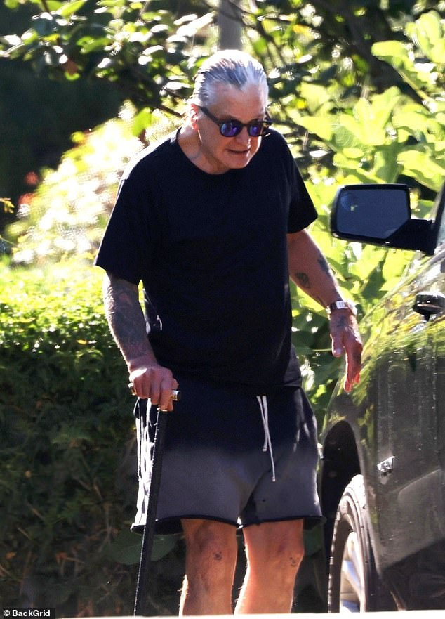 Outing: Ozzy Osborne Lukfreil using cane while walking in Santa Barbara on Monday amid his battle with Parkinson's disease