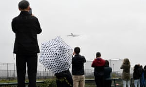 Viewers take photos of one of the departing planes