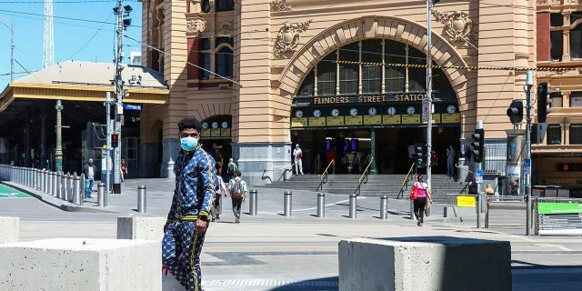 A man wearing a mask behind the Flinders Street station in Melbourne on Wednesday, October 28, 2020 in Australia.  Mel was allowed to open Australia's former coronavirus hotspots, restaurants, cafes and bars, and outdoor contact sports, which could resume on Wednesday, have emerged.  Lockdown due to coronavirus outbreak.  (AP Photo / Asanka Brendon Ratnayake)