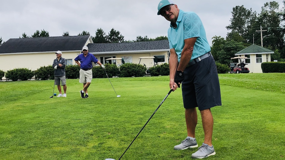 Dennis Houde prepares to hit the ball on the first hole of the golf course.