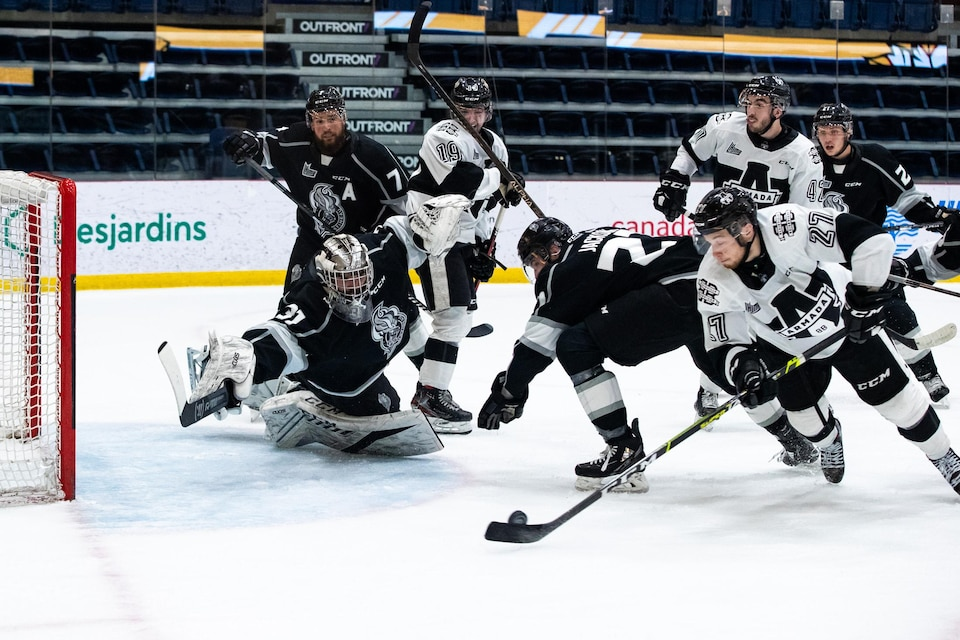 An Armada player prepares to throw the puck into an empty net as the failed Olympic goalkeeper tries to make a save in the extremists.