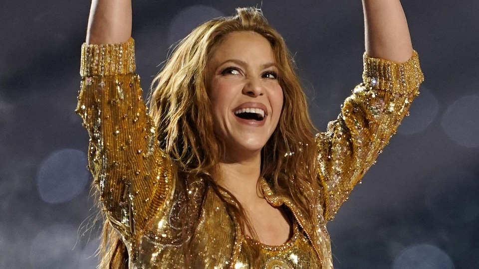 Shakira smiles and throws her arms in the air.